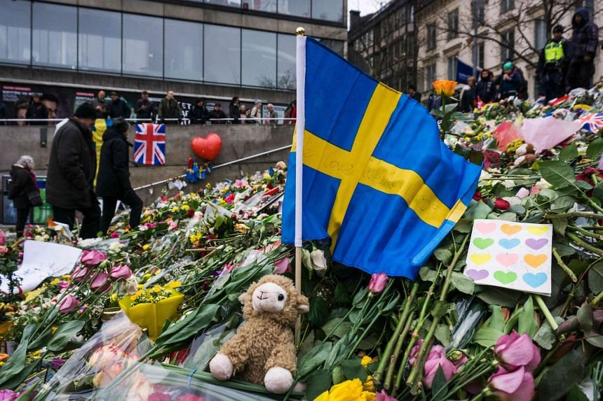People gather at a makeshift memorial to commemorate the victims of last Friday's terror attack near the site where a truck drove into Ahlens department store in Stockholm, on April 14, 2017.
