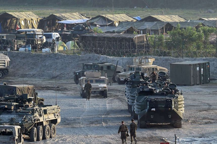 """This file photo taken on April 14, 2016 shows US marines walking next to their transport and amphibious vehicles at a temporary camp for the """"Balikatan"""" joint US-Philippine military exercise at Crow Valley, in Capas town, north of Manila."""
