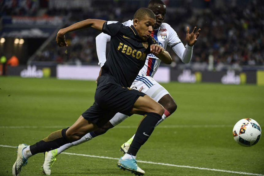 Monaco's French forward Kylian Mbappe Lottin (left) vies with Lyon's defender Mouctar Diakhaby (right) during the French L1 football match between Olympique Lyonnais and AS Monaco, on April 23, 2017 at Parc Olympique Lyonnais stadium.