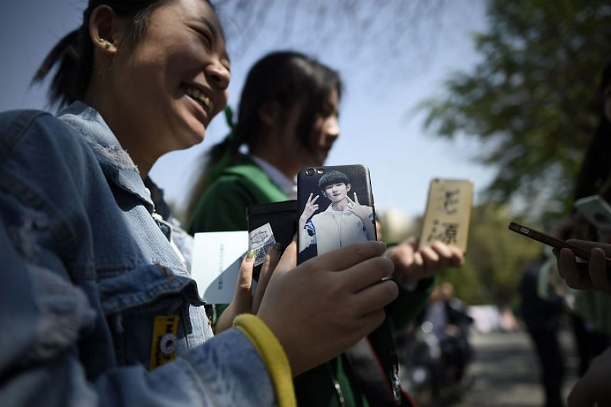 A woman holding her mobile phone carrying a picture of Roy Wang from China's boy band sensation TFBoys (The Fighting Boys) during an event for fans at a university in Beijing on April 14, 2017.