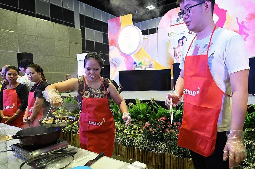 Ms Michelle Delos Santos Macaraeg (at the wok), 36, and her employer's son, Mr Darren Lee (right), 26, won the cooking competition.