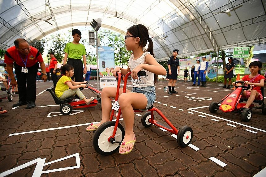 Children at the mini road safety circuit at AMK 3G Centre during a road safety carnival yesterday. Prime Minister Lee Hsien Loong, who is also an MP for Ang Mo Kio GRC, launched a locker service for residents to store their personal mobility devices