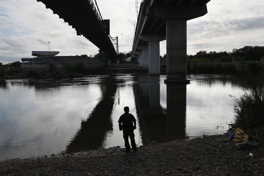 A US Border Patrol agent looks into Mexico from the bank of the Rio Grande on March 13, 2017, in Roma, Texas.