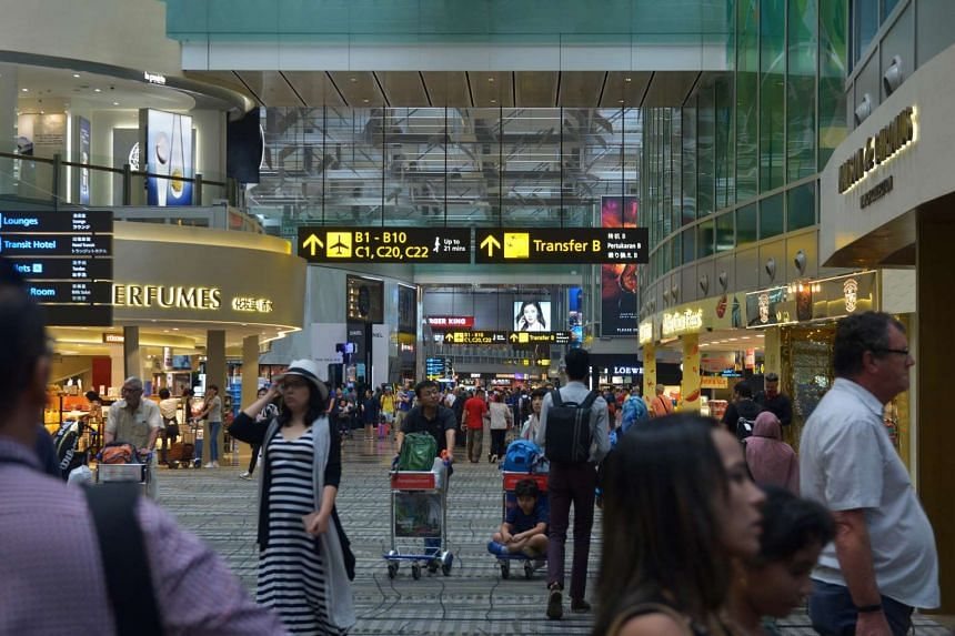 Travellers move through the duty-free shopping area in the transit lounge at Changi Airport's Terminal 3.