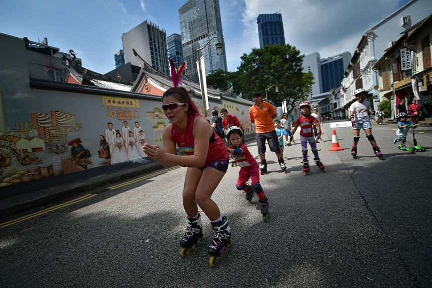 Families and friends playing during a roller blade game on Car-Free Sunday along Amoy Street on March 26, 2017.