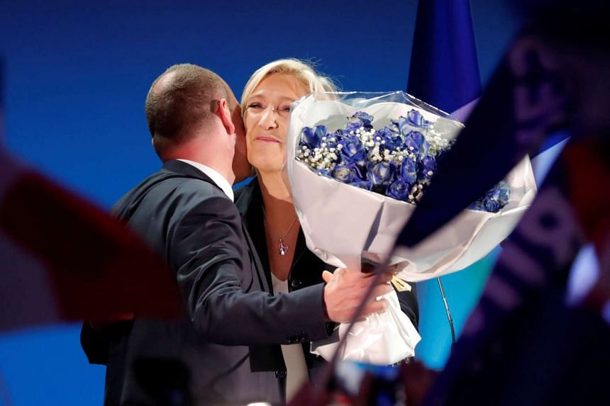 Mayor of Henin-Beaumont Steeve Briois gives a bouquet of flowers to Marine Le Pen, French National Front (FN) political party leader and candidate for French 2017 presidential election, as she celebrates after early results in the first round of 2017