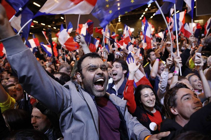 Supporters celebrate as French presidential election candidate for the 'En Marche!' (Onwards!) political movement, Emmanuel Macron (not in picture) finishes in first position of the first round of the French presidential elections in Paris, France, o
