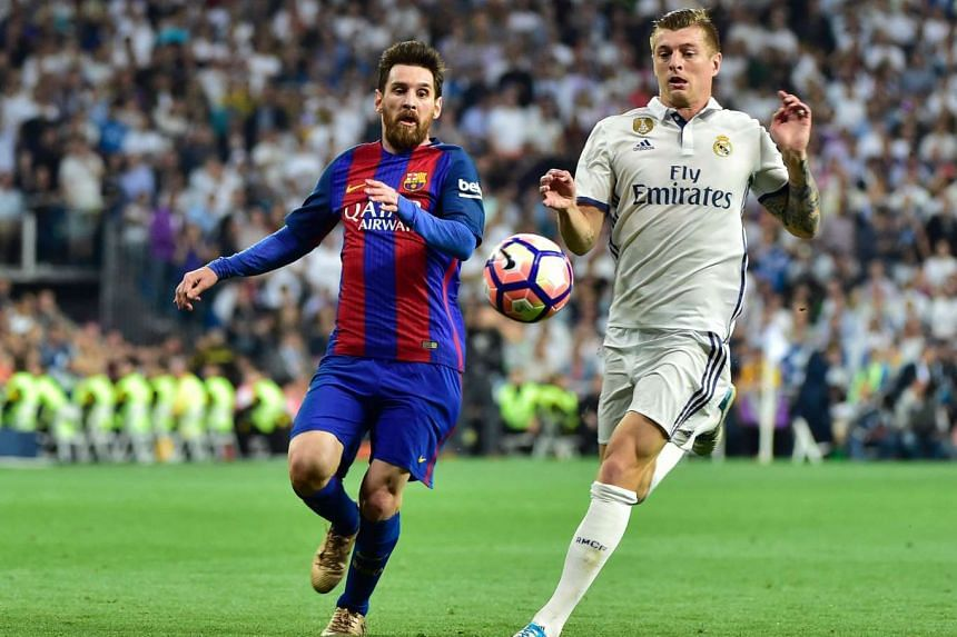 Barcelona's Argentinian forward Lionel Messi (left) vies with Real Madrid's German midfielder Toni Kroos during the Spanish league football match Real Madrid CF vs FC Barcelona at the Santiago Bernabeu stadium in Madrid on April 23, 2017.