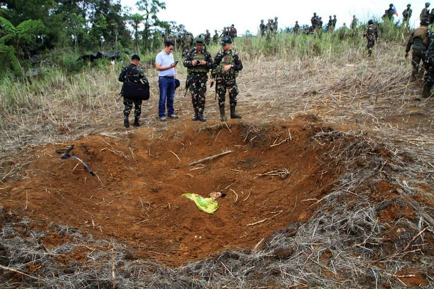 This photo taken on April 24, 2017 shows Philippine military officials inspecting a dead body, believed to be a member of Islamic State-affiliated extremists, buried inside a bomb crater after clashes with government troops in Piagapo town, Lanao del