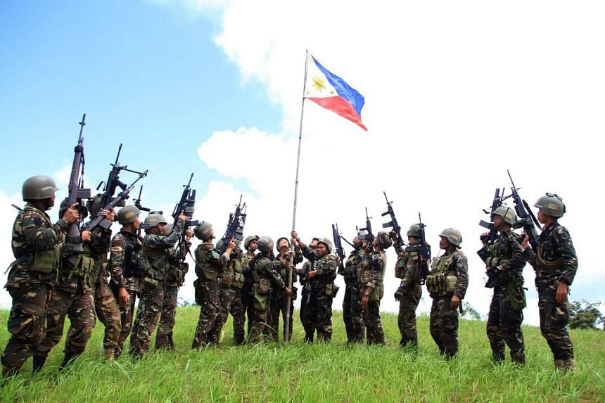 Philippine soldiers hoist a national flag after clashes with Islamic State-affiliated extremists in the mountain area of Piagapo town, Lanao del Sur province, on the southern island of Mindanao on April 25, 2017.