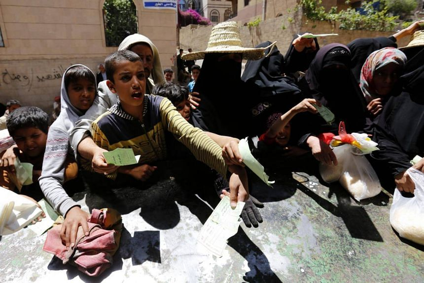 Conflict-affected Yemenis receive local charity-provided food rations in Sana'a, Yemen, on April 13,l 2017.