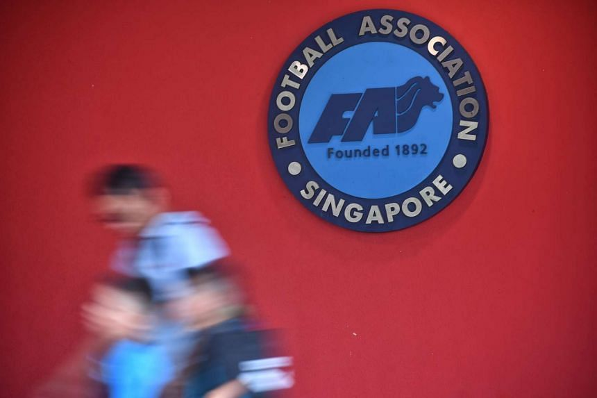 People walking past a Football Association of Singapore (FAS) logo outside the office at Jalan Besar Stadium on 22 April, 2017.