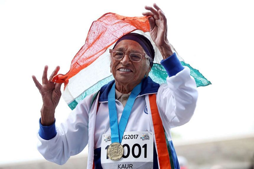 Man Kaur, 101, celebrates after competing in the 100m sprint in the 100+ age category at the World Masters Games in Auckland on April 24, 2017.