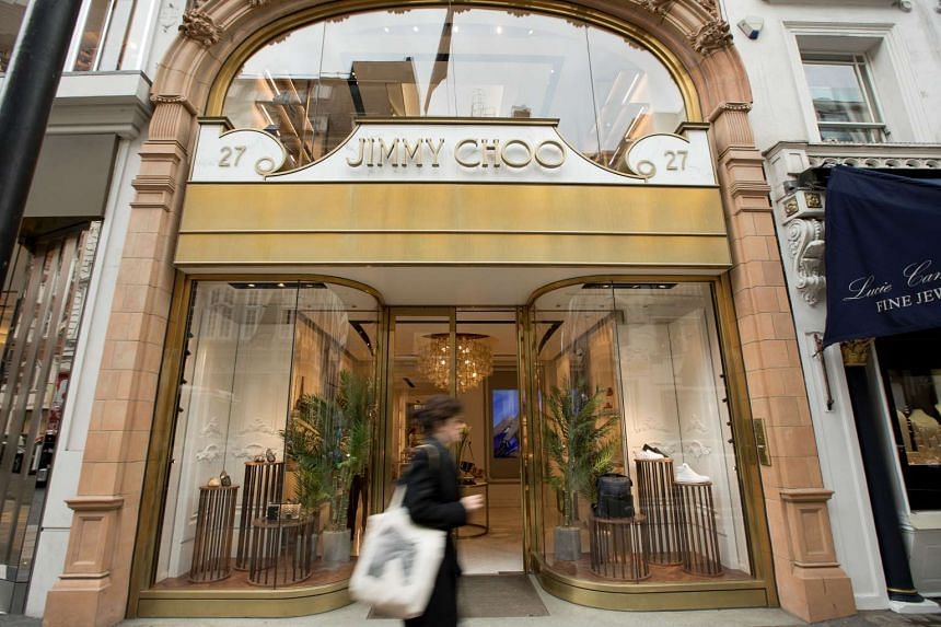 A pedestrian walks past a store of the luxury shoemaker Jimmy Choo in central London on April 24, 2017.