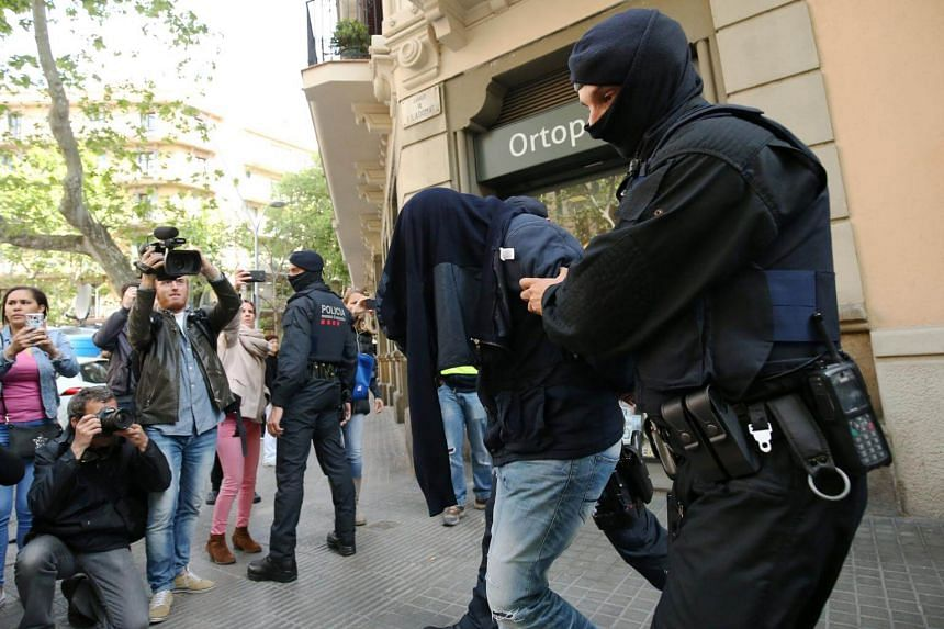 Spanish police lead a suspect from an apartment building during a sweeping operation at some 12 locations against Islamist militants in which eight people were arrested in Barcelona, Spain, on April 25, 2017.