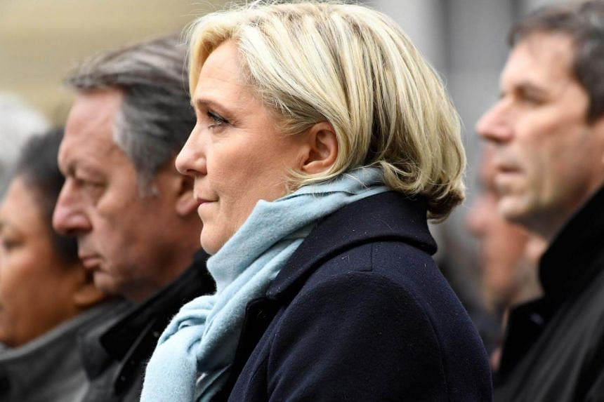 French presidential election candidate for the far-right Front National party, Marine Le Pen (front) and French Junior Sports Minister, Thierry Braillard (left) attend a ceremony honouring the policeman killed by a jihadist in an attack on the Champs