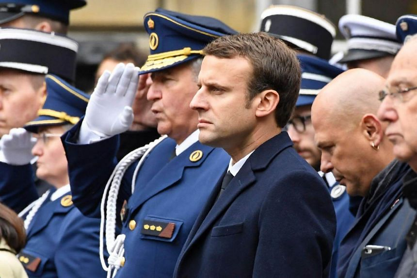 French presidential election candidate for the En Marche ! movement, Emmanuel Macron (centre) attends a ceremony honouring the policeman killed by a jihadist in an attack on the Champs Elysees, on April 25, 2017.