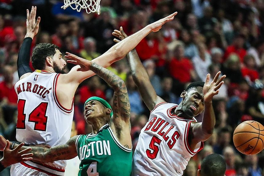 Boston Celtics guard Isaiah Thomas is thwarted under the basket by Chicago Bulls forwards Nikola Mirotic and Bobby Portis during the 104-95 Game Four victory.