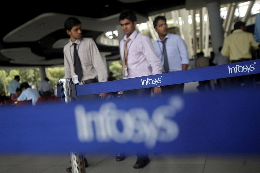 Employees of Indian software company Infosys walk past Infosys logos at their campus in the Electronic City area in Bengaluru, India, on Sept 4, 2012.