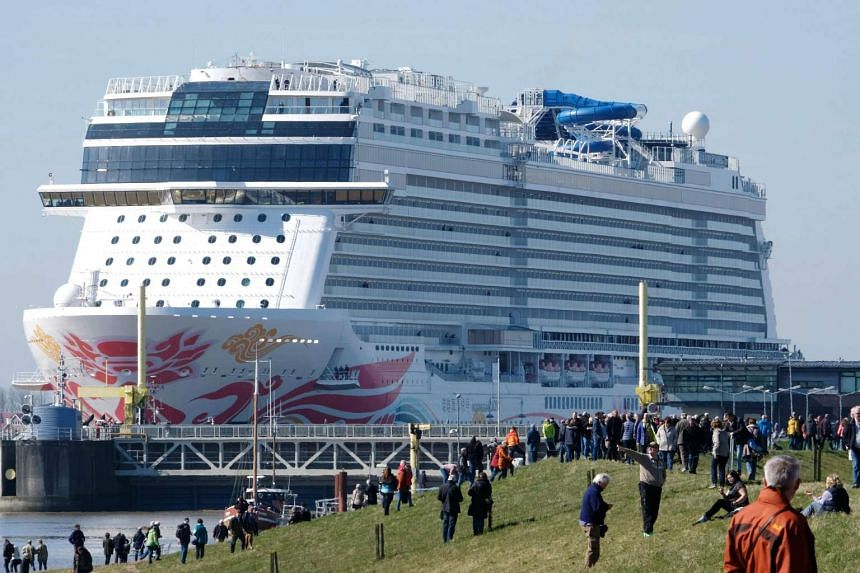 Spectators look on as the Norwegian Joy cruise ship passes a shipping lock to make its way over the river Ems near Emden, northern Germany.
