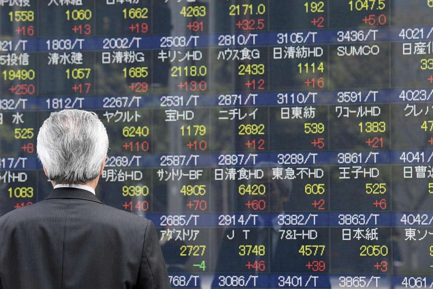 A businessman looking at an electronic share indicator at the window of a securities company in Tokyo.