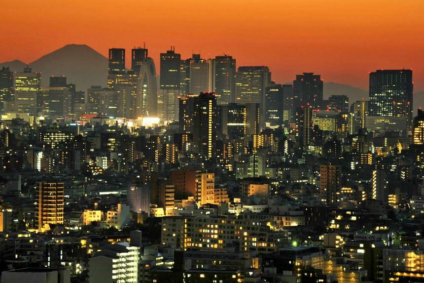 Japan's Mount Fuji rising up behind the skyscrapers dotting the skyline of the Shinjuku area of Tokyo at sunset.