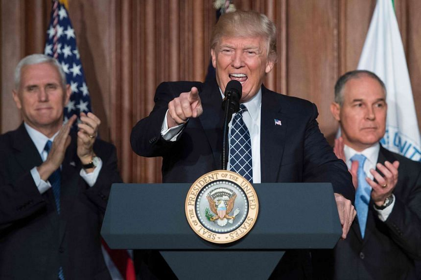 US President Donald Trump (centre) speaking before signing the Energy Independence Executive Order at the Environmental Protection Agency (EPA) Headquarters in Washington, DC, on March 28, 2017, with Vice President Mike Pence (left) and Environmental