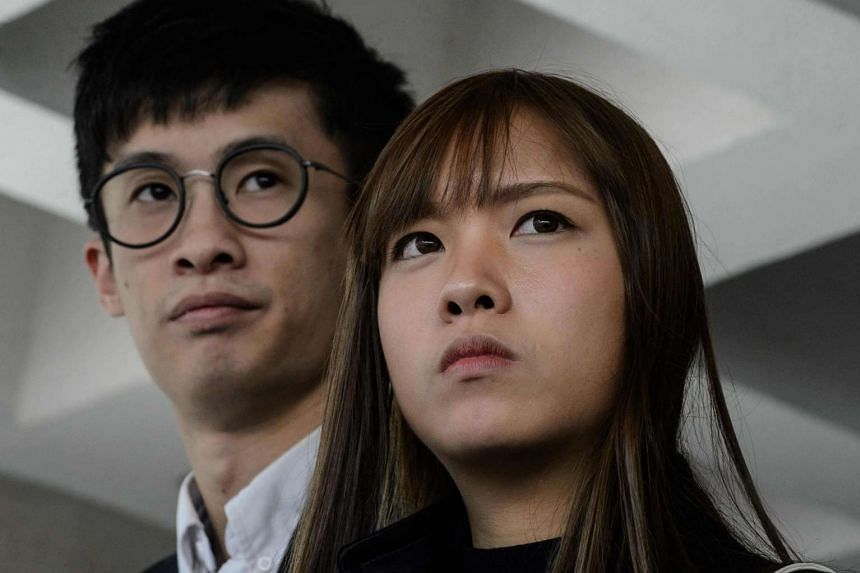 Disqualified Hong Kong lawmakers Baggio Leung (left) and Yau Wai Ching were arrested and taken to a police station for questioning on April 26, 2017.