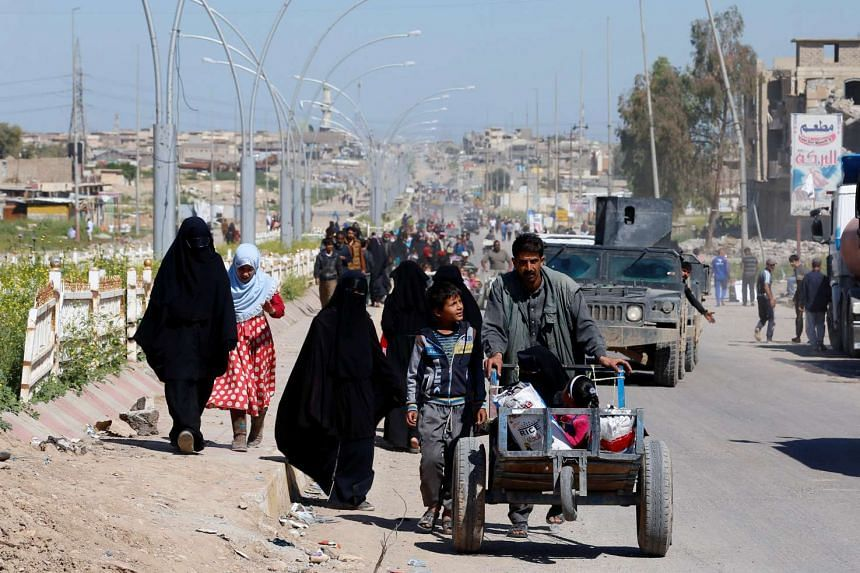 Displaced Iraqis flee during a fight between Iraqi Counter Terrorism Service forces and ISIS militants in western Mosul, April 25, 2017.