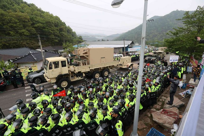 Protesters and police standing by as trailers carrying US Thaad missile defence equipment enter a deployment site in Seongju, on April 26, 2017.