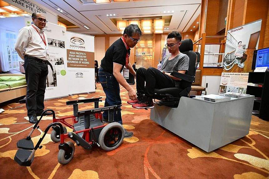 Managing director of Radiance Medical Systems Steven Ho, 51, demonstrating how to retract the wheel so that a user can move smoothly out of a transfer wheelchair into a chair, watched by managing director of Winner SG Michael Pang, 66. The world's fi