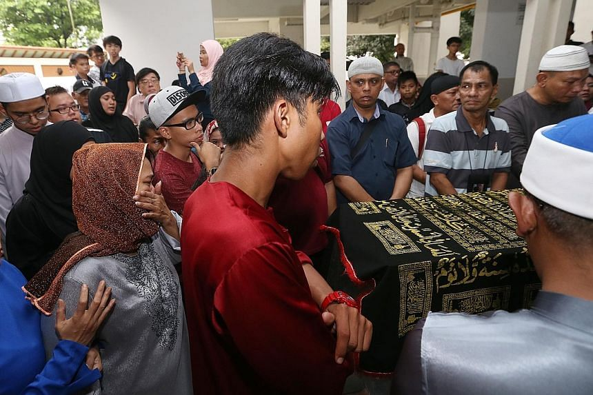 Some of Hambali's schoolmates and teachers arriving to bid him a final farewell yesterday. His friends from kindergarten and primary school, as well as his youth soccer club teammates, were also present. Madam Rajimah Jafar being consoled as family a