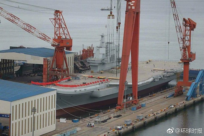 Red flags line the flight deck of China's first locally-built aircraft carrier, which is expected to be launched soon.