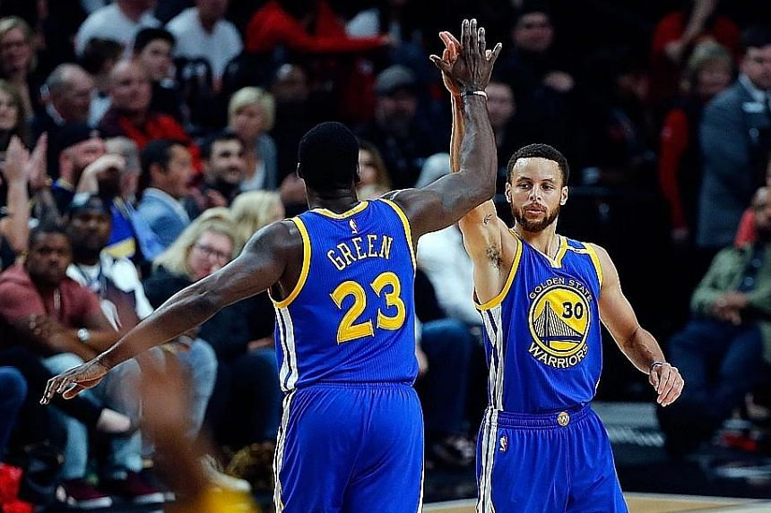 Stephen Curry giving his Warriors team-mate Draymond Green a high-five after sinking one of his seven three-pointers against the Trail Blazers. Golden State swept Portland 4-0 to become the first team to reach the second round of the play-offs.