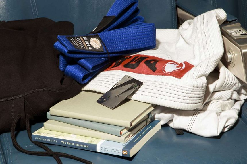 Travel necessities for celebrity chef Anthony Bourdain: his jujitsu belt and gi, books about his destination, Moleskine notebooks and a credit card concealing a knife.
