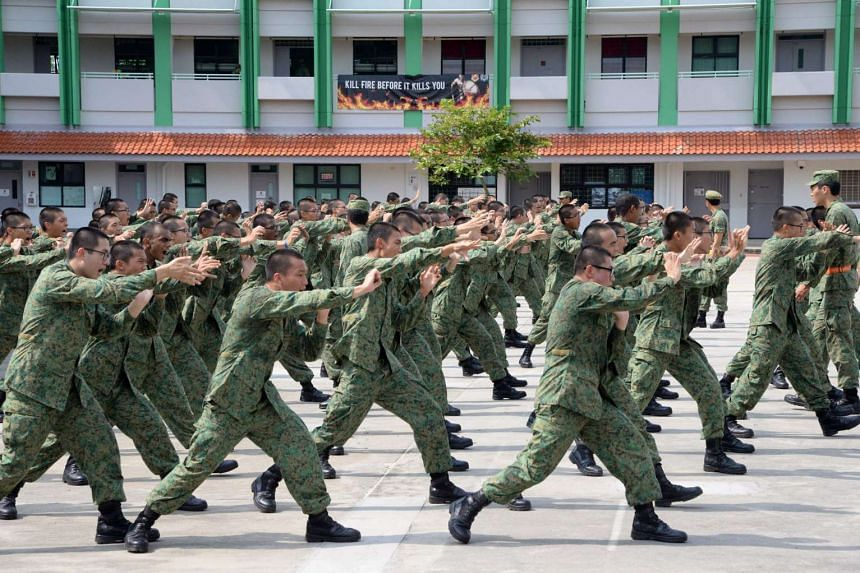 Service recruits demonstrate hand-to-hand combat moves as part of their two-month long basic training on Pulau Tekong off Singapore on Feb 7, 2017.