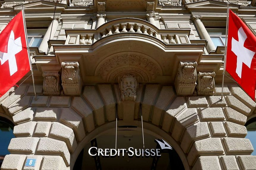 Switzerland's national flags fly beside the logo of Swiss bank Credit Suisse, on April 24, 2017.