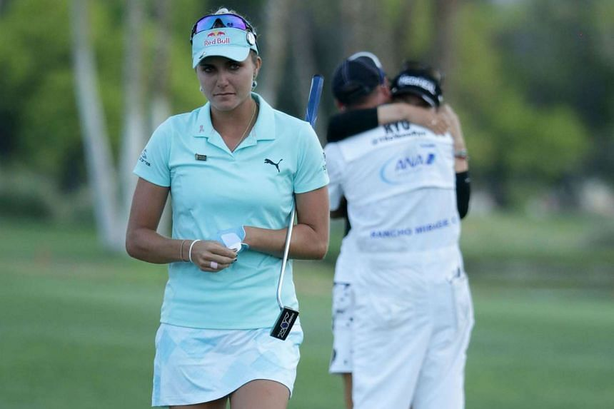 Lexi Thompson walks off the 18th green as So Yeon Ryu of the Republic of Korea celebrates with her caddie, after Ryu defeated her in a playoff during the final round of the ANA Inspiration at the Dinah Shore Tournament Course in California on April 2