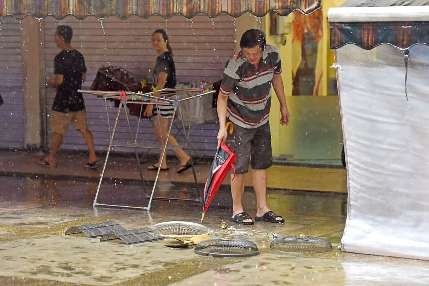 A man washing his wares with rainwater during a heavy downpour at Block 37, Circuit Road, at noon yesterday. Keep the umbrella handy as the prevailing inter-monsoon conditions over Singapore are expected to persist and extend into next month. Moderate to