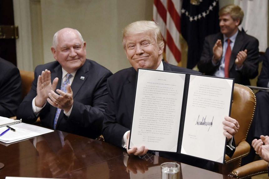 US President Donald Trump (right) holds up the Executive Order Promoting Agriculture and Rural Prosperity in America during a roundtable with farmers at the White House.