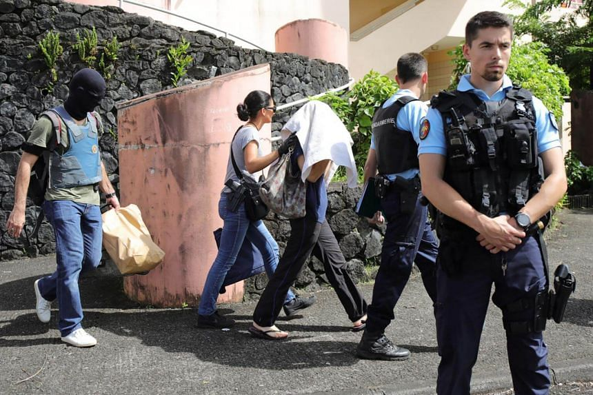 French gendarmes and police officers escort a person (centre, hidden face)  on April 27, 2017 in Saint-Denis-de-la-Reunion, on the French Indian Ocean island of Reunion, after a man suspected of being a radicalised Islamist shot and wounded two polic
