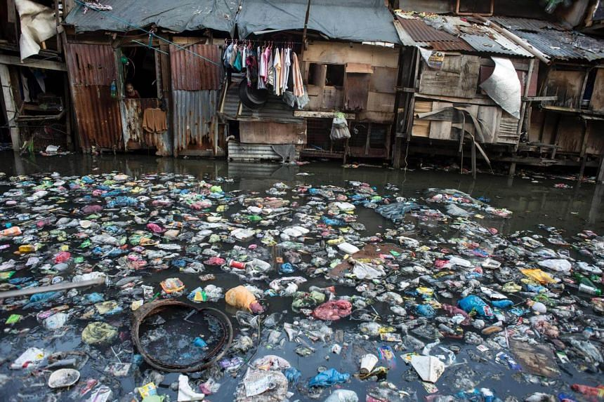 A girl peeks from the window of a house beside a polluted creek in Manila on March 22, 2017.