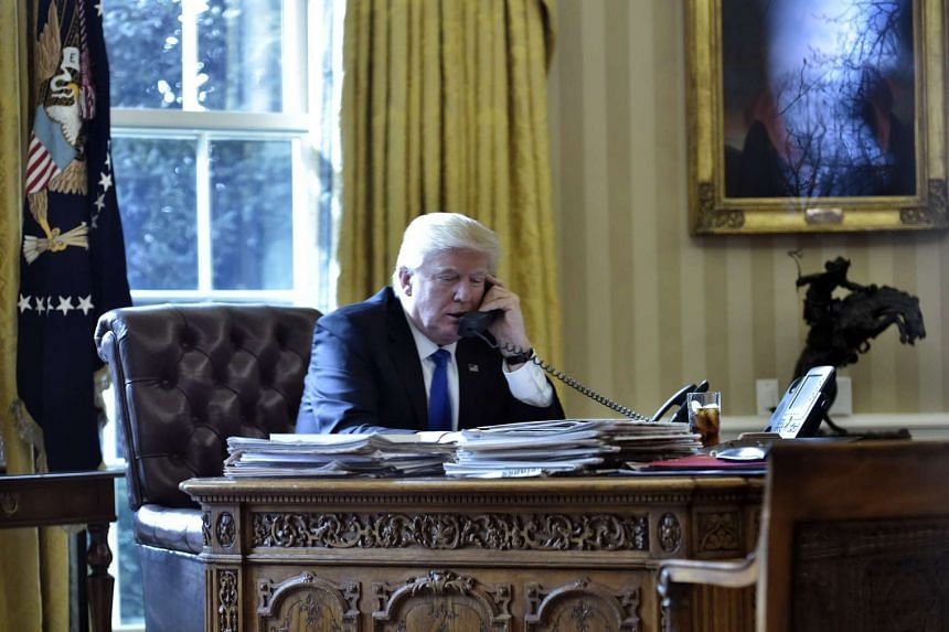 US President Donald Trump speaking on the phone in the Oval Office.