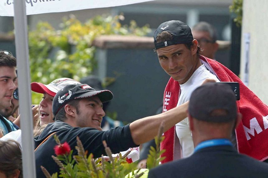 Nadal signs autographs after his training in Barcelona.