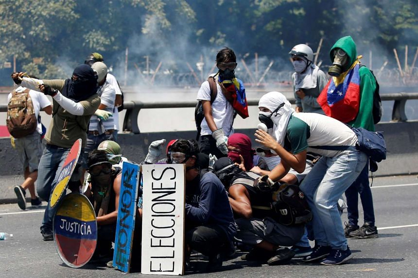 Opposition supporters clash with security forces in Caracas, April 26, 2017.