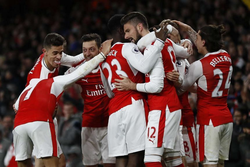 Arsenal's players celebrate after Leicester City's Robert Huth scores an own goal.