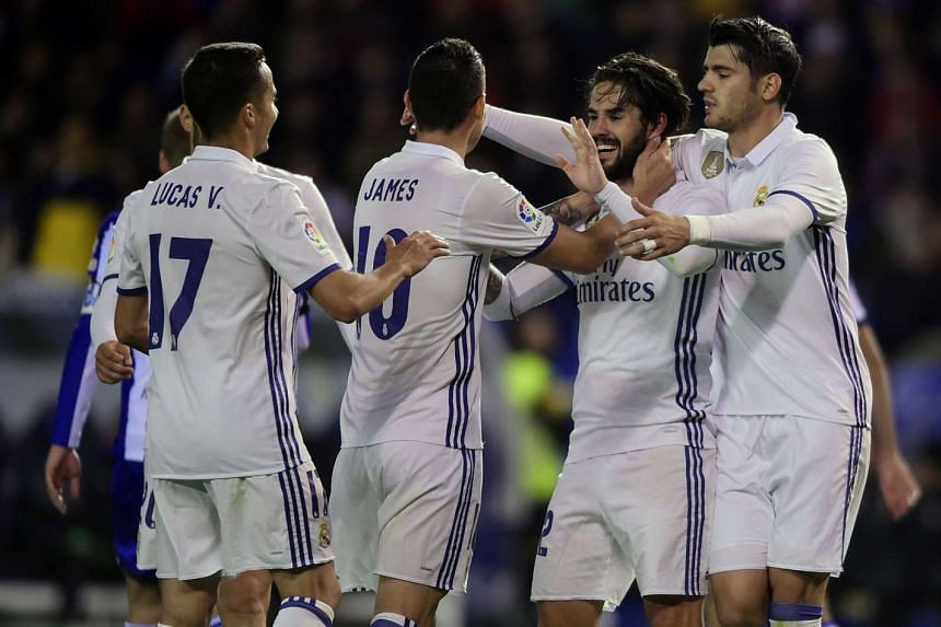 Real Madrid's midfielder Isco (second right) celebrates with teammates after scoring a goal.