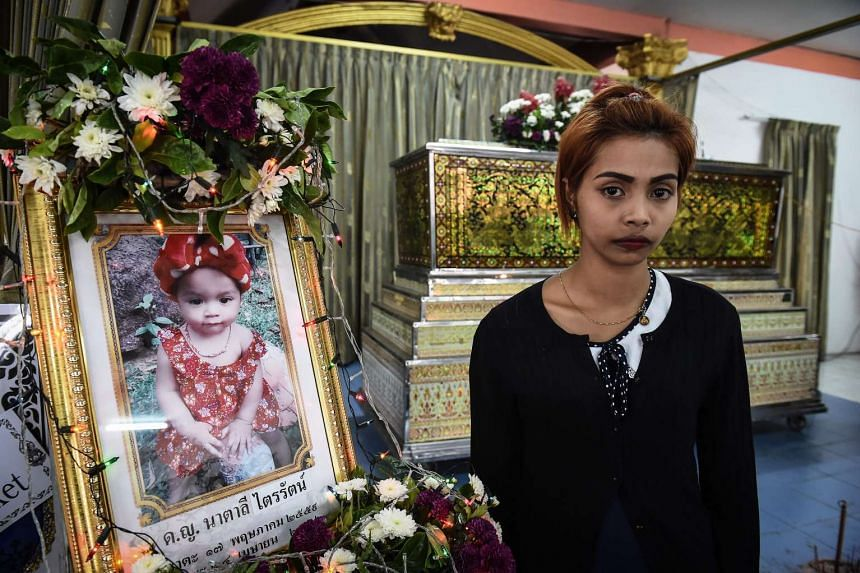 Jiranuch Trirat, 22, stands in front of the coffin of her slain 11-month-old daughter Natalie at a temple in Phuket on April 27, 2017.