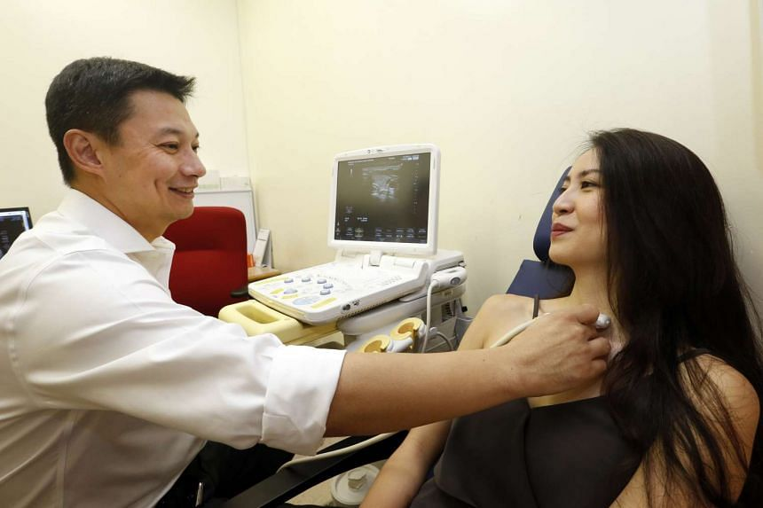 Dr Jeremy Ng, head and senior consultant, Department of General Surgery of SGH and a female patient on a scar-free thyroid procedure.