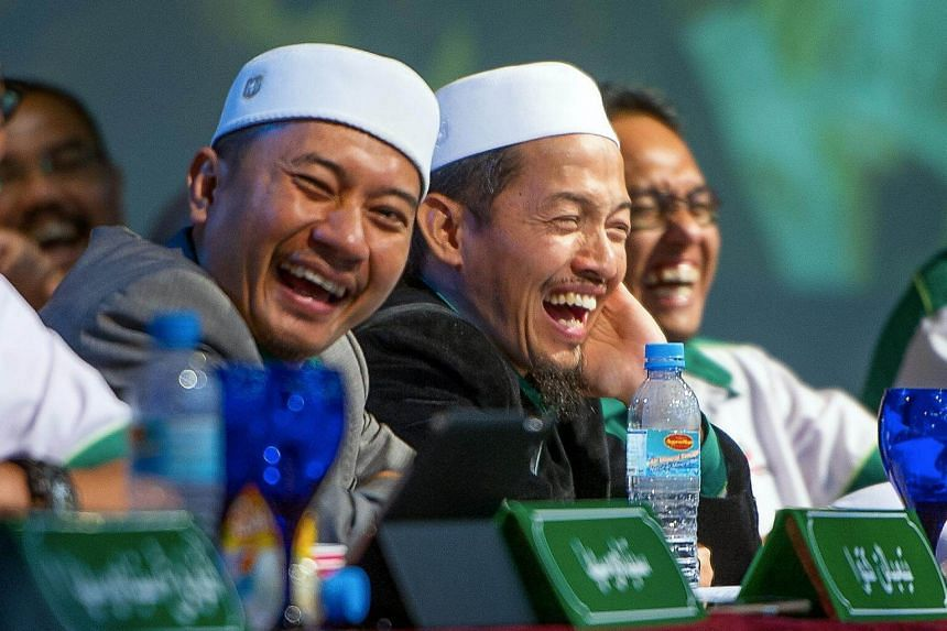 PAS Youth Chief Mohamad Abduh Nik Abdul Aziz (middle) with his deputy Muhammad Khalil Abdul Hadi (left) laughing at the annual congress of PAS Youth.